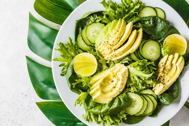 Insalata verde del cetriolo e dell'avocado in zolla bianca. menù disintossicante, cibo vegano, dieta a base vegetale.
