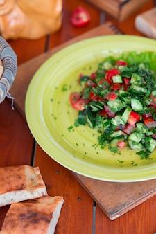 Insalata verde di verdure, salati di choban in piatto verde.
