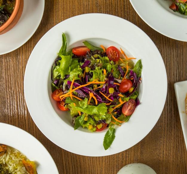 Insalata verde fresca d'estate con erbe e pomodori.