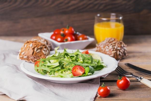 Insalata verde, pomodori, pane integrale e succo d'arancia su legno.