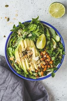 Insalata verde sana con avocado, ceci al forno e semi in ciotola bianca, vista dall'alto.
