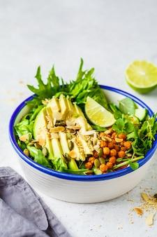 Insalata verde sana con avocado, ceci al forno e semi in ciotola bianca.