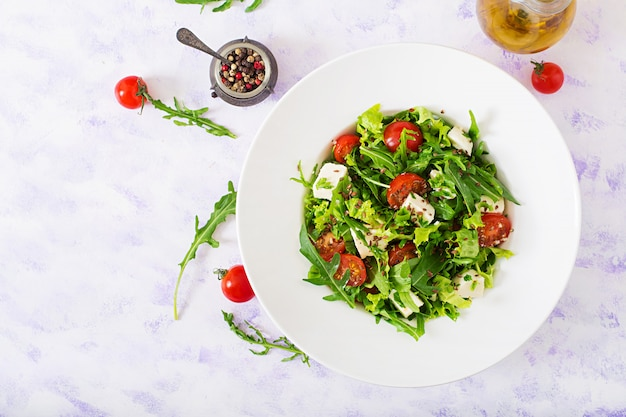 Insalata vitaminica di pomodori freschi, rucola, formaggio feta e peperoni. menu dietetico. nutrizione appropriata. vista dall'alto. disteso.
