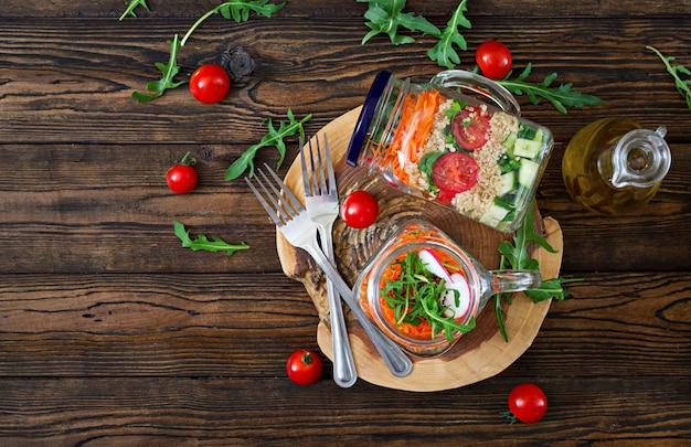 Insalate con quinoa, rucola, ravanello, pomodori e cetrioli in barattoli di vetro sul retro in legno