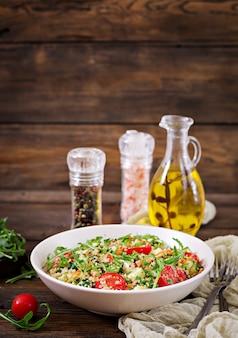 Insalate con quinoa, rucola, ravanello, pomodori e cetrioli in ciotola su fondo di legno.
