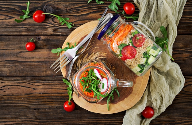 Insalate con quinoa, rucola, ravanello, pomodori e cetriolo in barattoli di vetro sulla tavola di legno. cibo sano, dieta, disintossicazione e concetto vegetariano. vista dall'alto. disteso