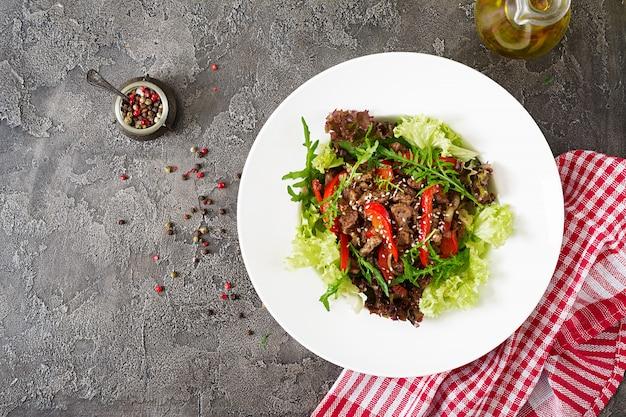 Insalatiera con carne di manzo, peperoni, cipolle e verdure miste, lattuga, rucola