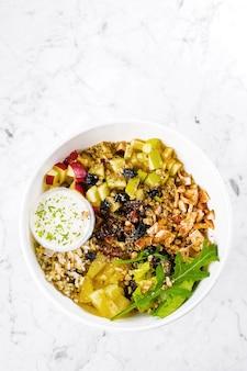 Insalatiera con insalata mista, petto di pollo, mela, ananas, lievito, datteri, riso integrale e noci. insalata di keto in ciotola su marmo.