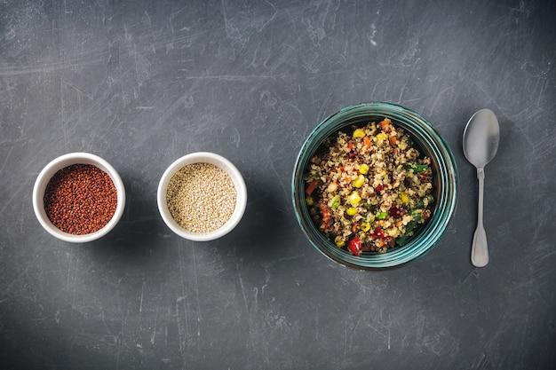 Insalatiera di quinoa con verdure colorate, semi di quinoa bianchi e rossi.