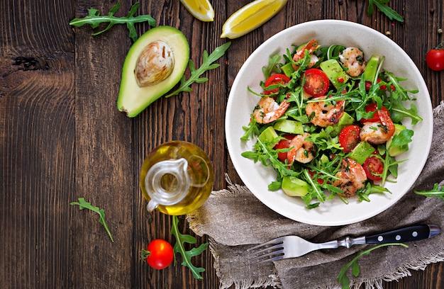 Insalatiera fresca con gamberetto, il pomodoro, l'avocado e la rucola sulla fine di legno della tavola su. cibo salutare. mangiare pulito. vista dall'alto. disteso.