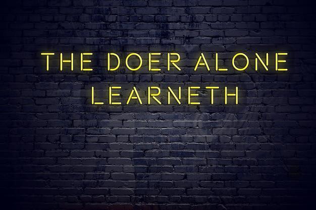 Insegna al neon con la citazione motivazionale saggia positiva contro il muro di mattoni