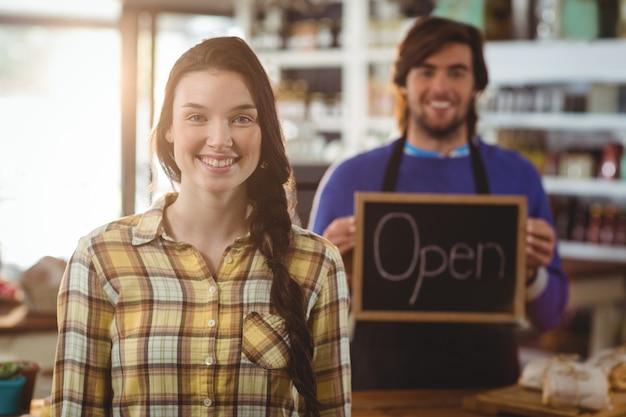 Insegna aperta della tenuta del cameriere e stare con il cliente