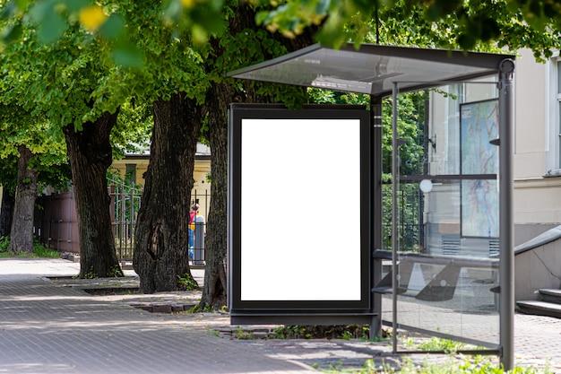 Insegna bianca in bianco di pubblicità ad una fermata di trasporto pubblico di un filobus nella città vicino al parco