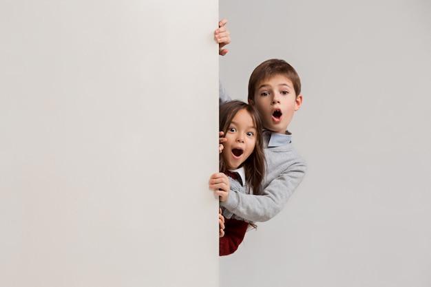 Insegna con bambini sorpresi che danno una occhiata al bordo