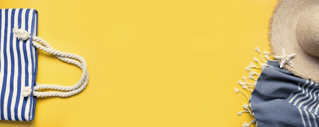Insegna della borsa della spiaggia, cappellino da sole della paglia, asciugamano di spiaggia su giallo. vacanze estive sullo sfondo. vista dall'alto