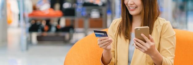 Insegna della donna asiatica che usando la carta di credito con il telefono cellulare per acquisto online nel grande magazzino