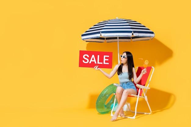 Insegna della donna asiatica sorpresa in attrezzatura di estate che mostra il segno di vendita