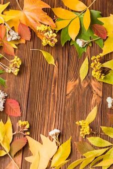 Insegna di autunno con le foglie variopinte dell'albero e fiori asciutti su legno marrone