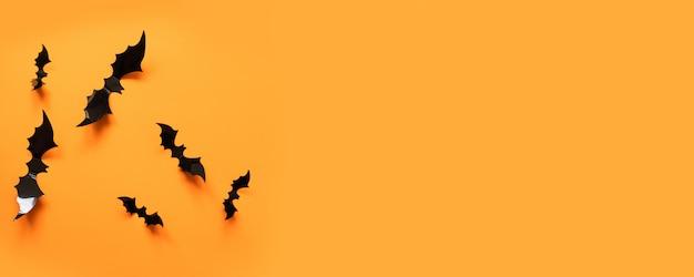 Insegna di halloween con i pipistrelli neri su superficie arancio, vista superiore