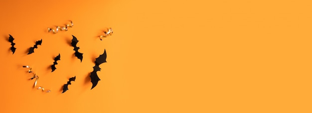 Insegna di halloween con i pipistrelli neri su una superficie arancio, vista superiore.