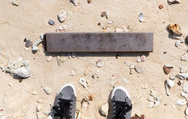 Insegna di legno vuota contro la spiaggia di sabbia tropicale