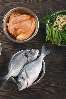 Insegna di panorama con gli ingredienti sani dell'alimento per animali domestici in singole ciotole su di legno marrone.