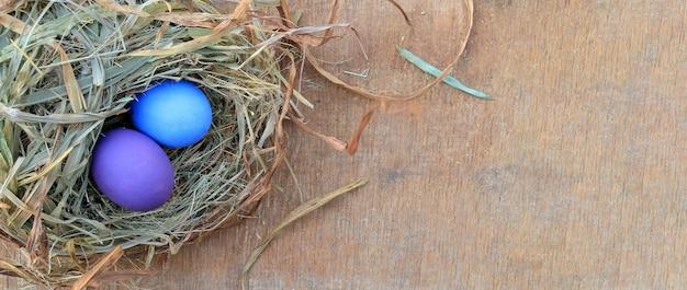 Insegna il fondo con lo spazio della copia, uova di pasqua variopinte su fondo di legno