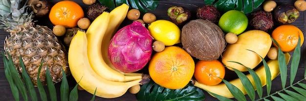 Insegna tropicale di frutti tropicali dell'arcobaleno con le foglie di palma sulla tavola di legno blu