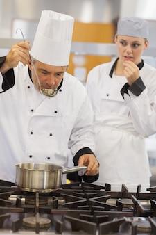 Insegnante che assaggia la sua zuppa di studenti con lei che guarda con ansia