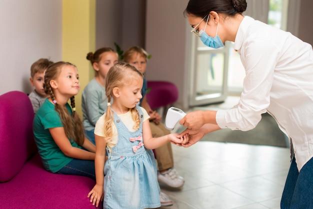 Insegnante che controlla la temperatura dei suoi studenti in tempo di pandemia