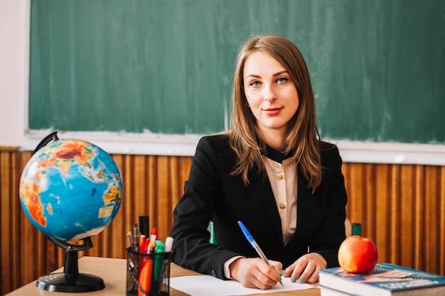 Insegnante che guarda l'obbiettivo mentre seduto alla scrivania