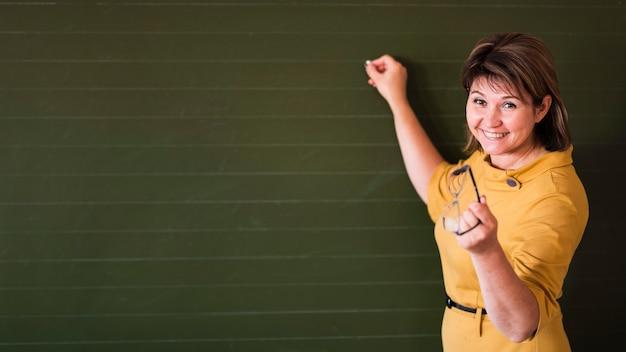 Insegnante che indica alla lavagna con copia-spazio