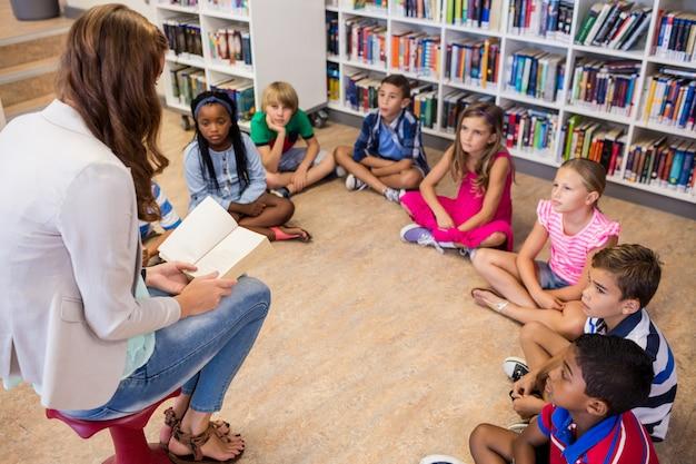Insegnante che legge libri ai suoi studenti
