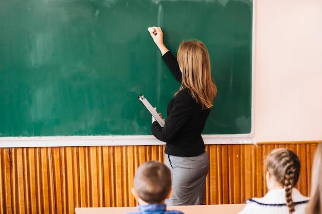 Insegnante che scrive con il gesso