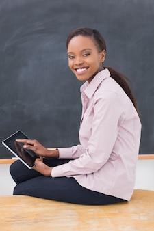 Insegnante che si siede sulla scrivania mentre si tiene un tablet pc