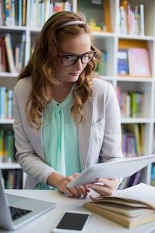 Insegnante che utilizza compressa digitale con il computer portatile e telefono sulla tavola nella biblioteca