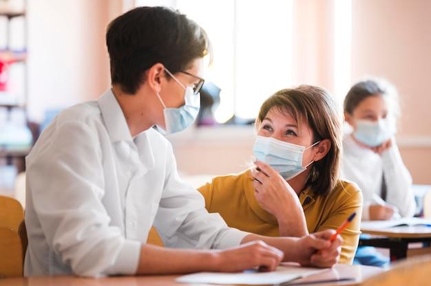 Insegnante con maschera che spiega classe