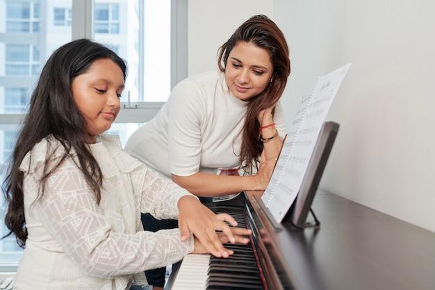 Insegnante con studente che suona il pianoforte