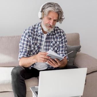 Insegnante del metà di colpo che esamina taccuino vicino al computer portatile