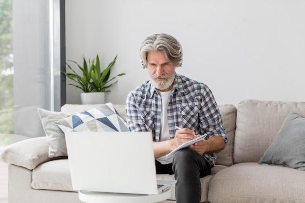 Insegnante del mezzo colpo che esamina computer portatile e che annota