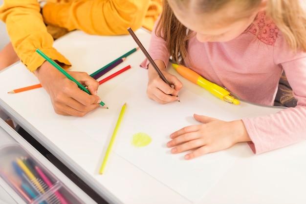 Insegnante di alto angolo che aiuta uno studente in classe