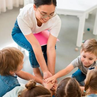 Insegnante di alto angolo che gioca con i suoi studenti