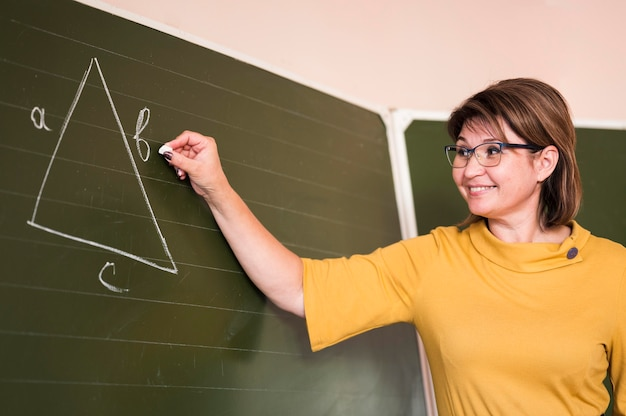 Insegnante di angolo basso che scrive sulla lavagna