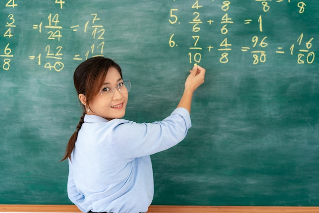 Insegnante di insegnante elementare asiatico che spiega la matematica in lavagna che dà la classe di scuola a distanza online