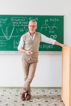 Insegnante di matematica invecchiato fiducioso guardando classe