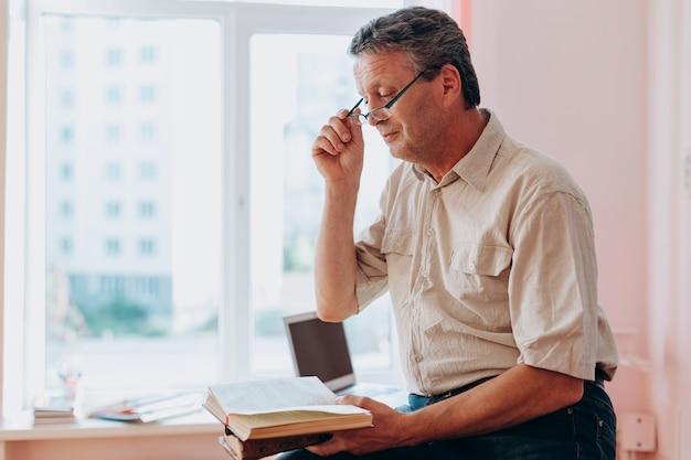 Insegnante di mezza età con gli occhiali seduto e leggendo un libro di testo.