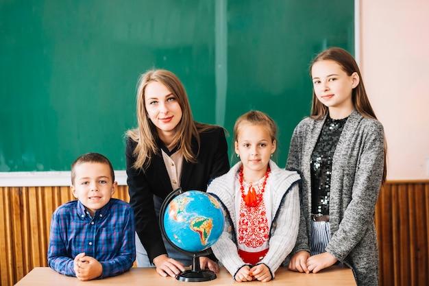 Insegnante di scuola femminile e studenti in piedi con il globo