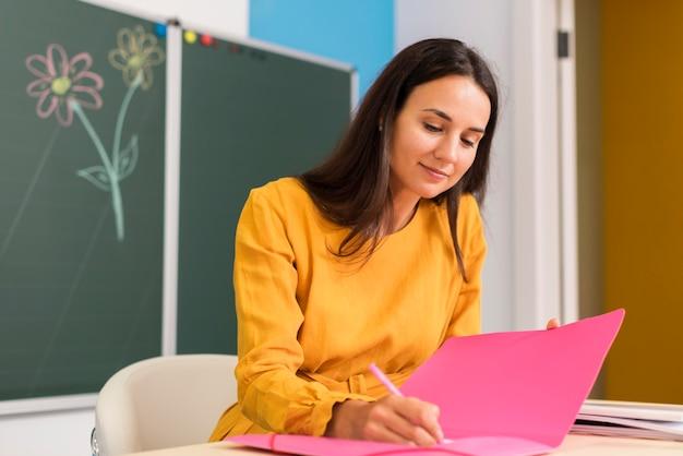 Insegnante di smiley che prende appunti