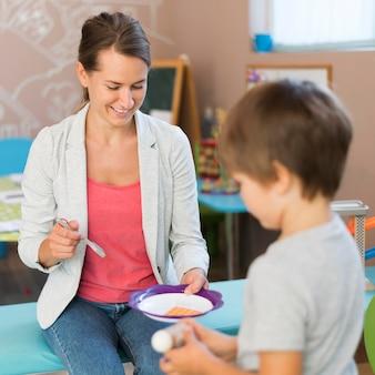 Insegnante di smiley e bambino che giocano insieme