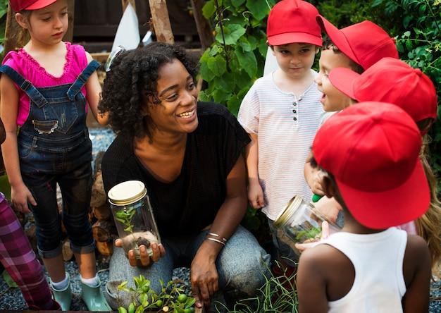 Insegnante e bambini che si divertono imparando a conoscere le piante